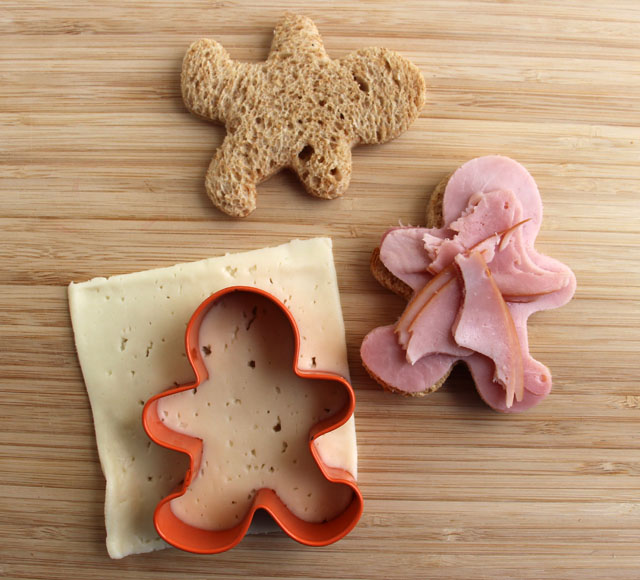 "Make a ""gingerbread"" sandwich by cutting bread, ham and cheese with a gingerbread shaped cookie cutter."